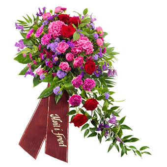 Funeral spray in cerise, purple and red colours.